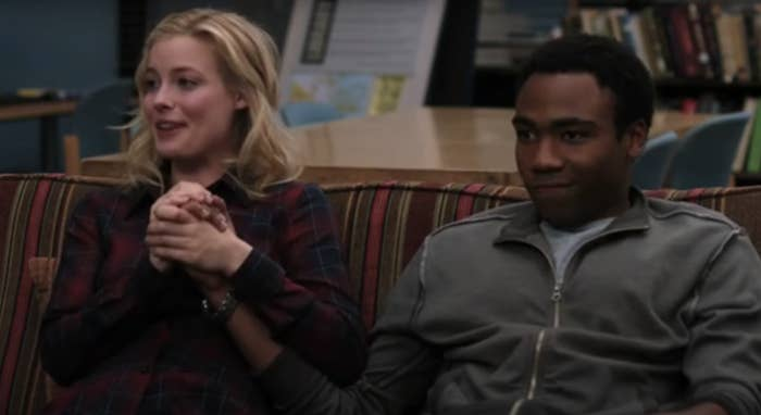 Britta holding Troy's hand as they sit on a couch