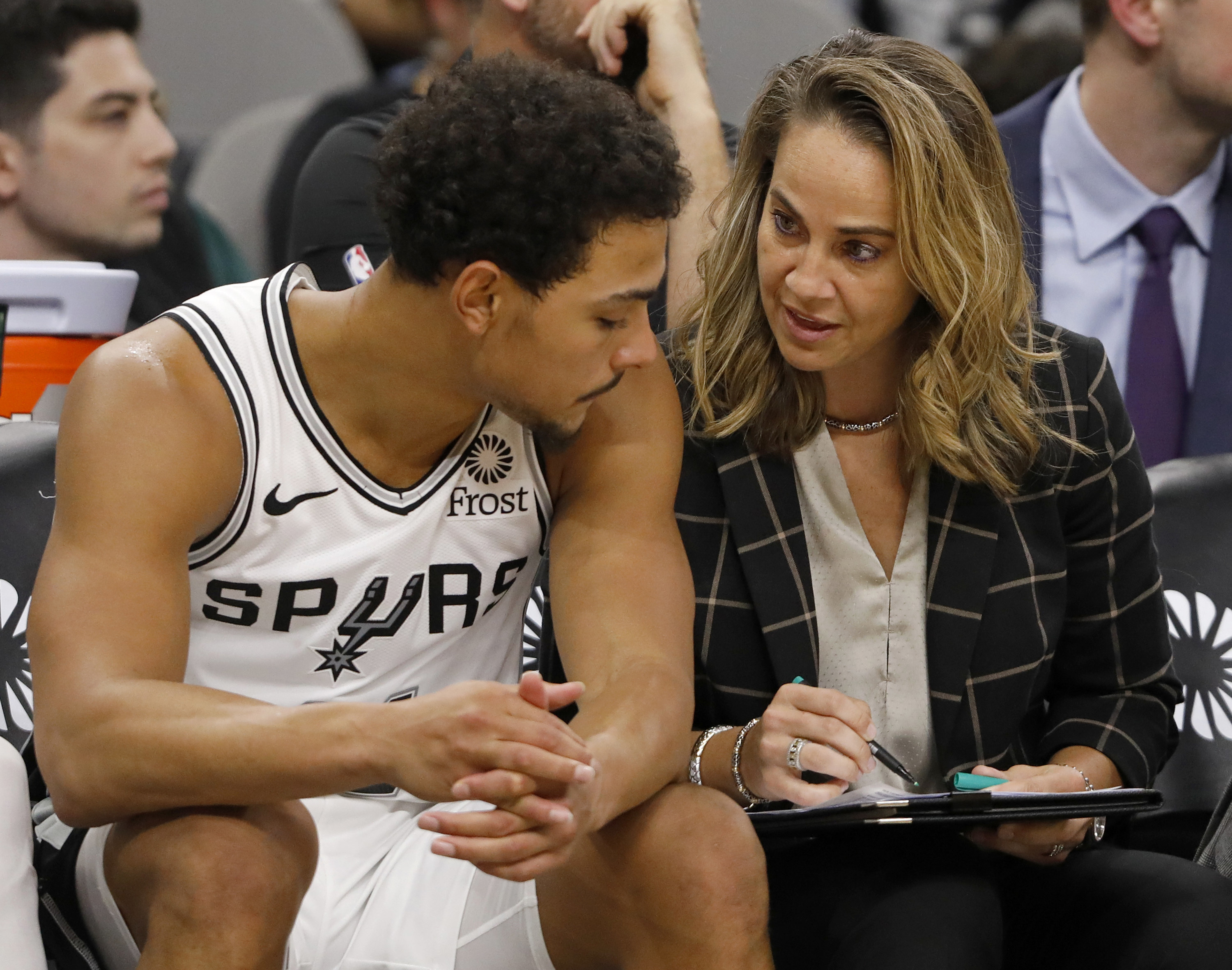 Becky Hammon sitting with a clipboard and talking to a Spurs player