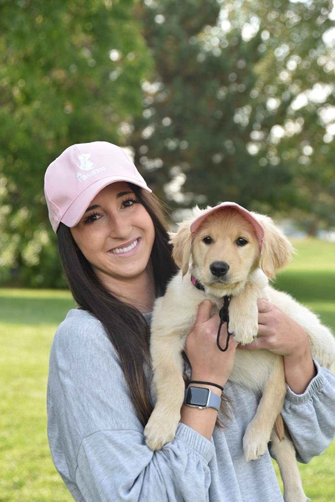 image of reviewer holding up a puppy, both of them wearing matching pink baseball hats