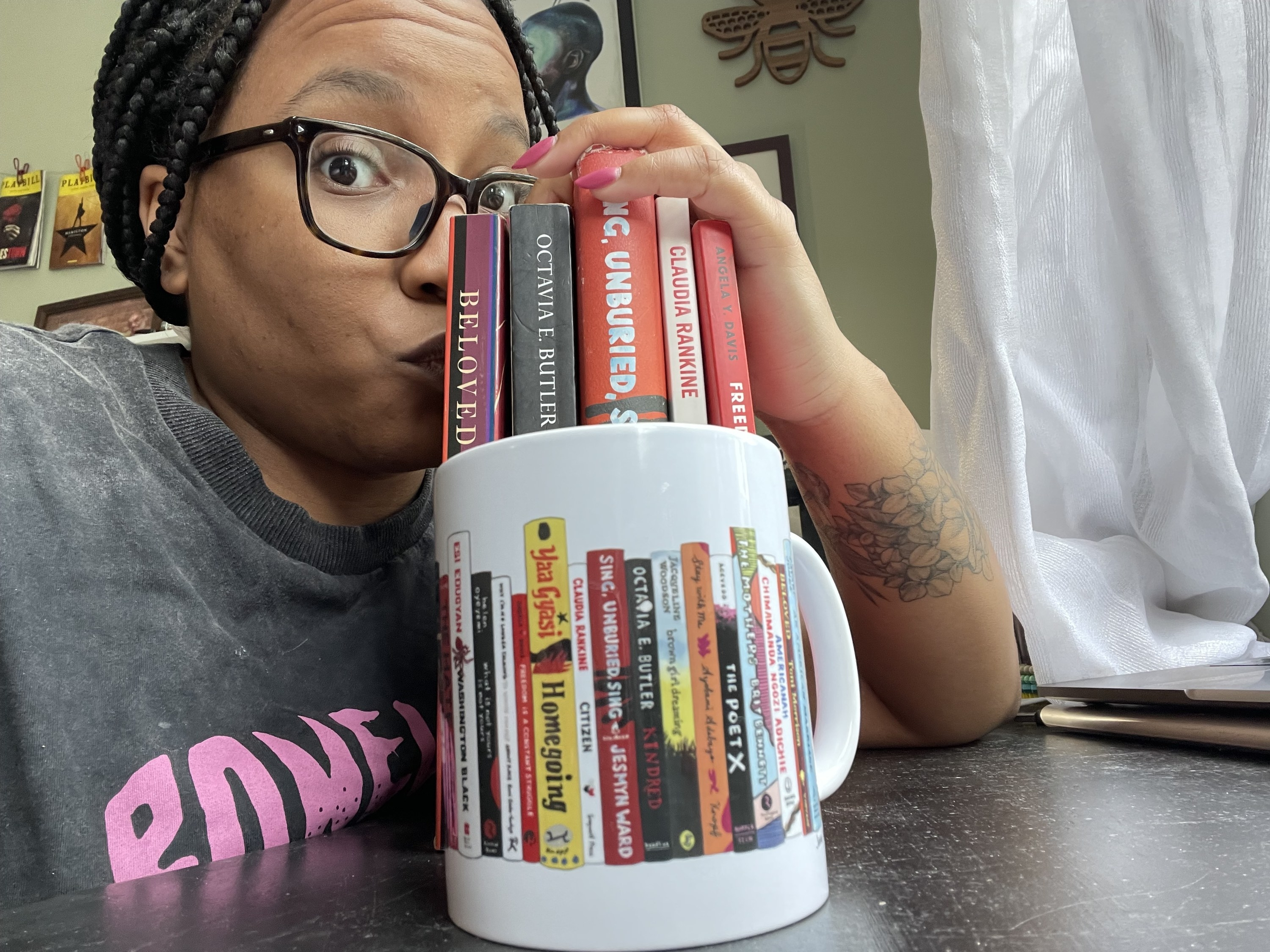 buzzfeed writer Taylor kissing a stack of books that mirror the books featured on the spines and vines mug