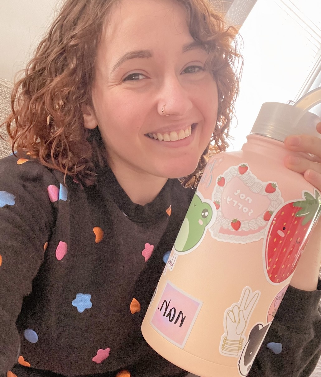 A person smiling while holding a pink water bottle with stickers on it