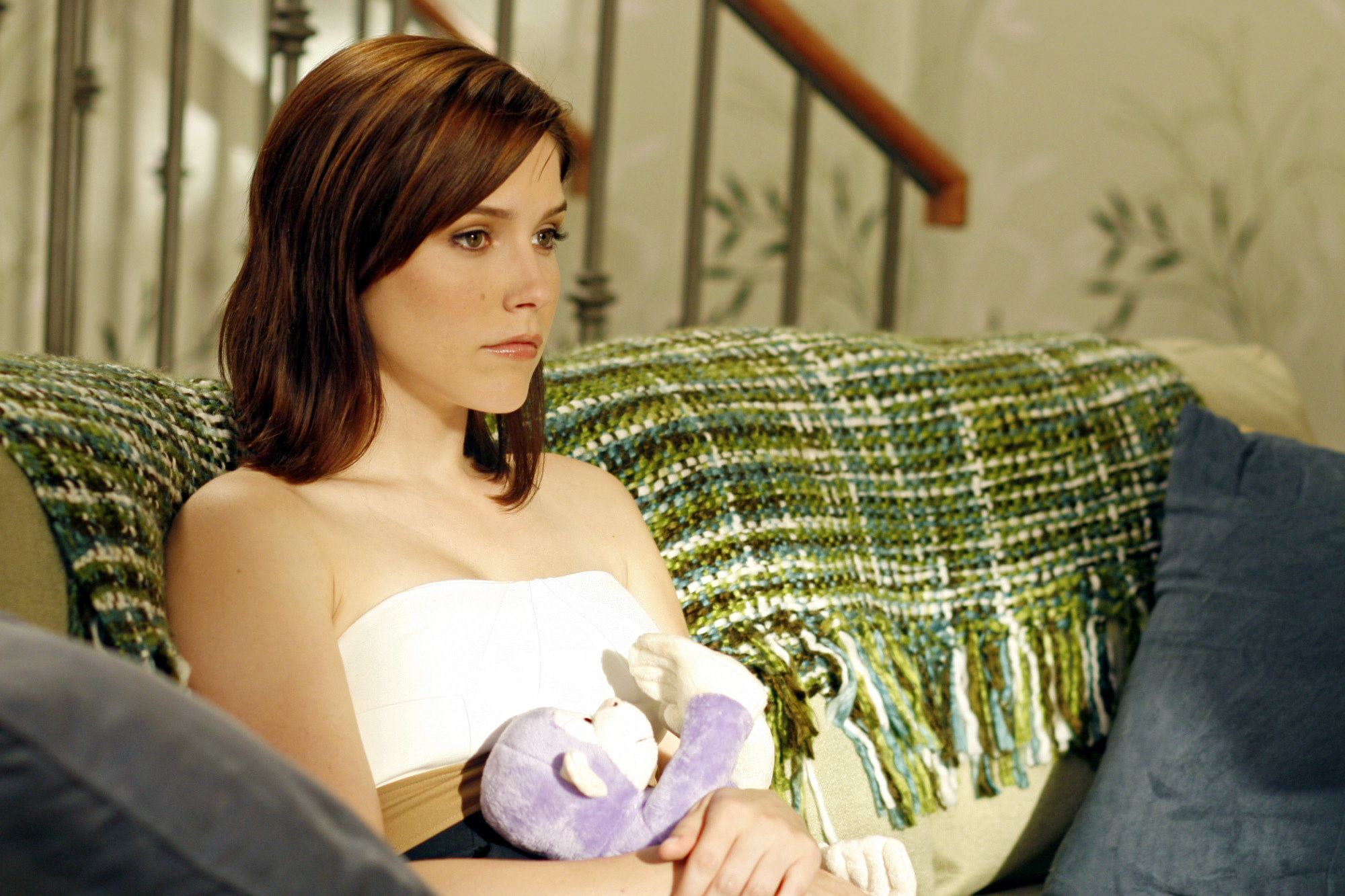 On the set of One Tree Hill, Sophia Bush sits on a couch, clutching a monkey stuffed animal, looking concerned