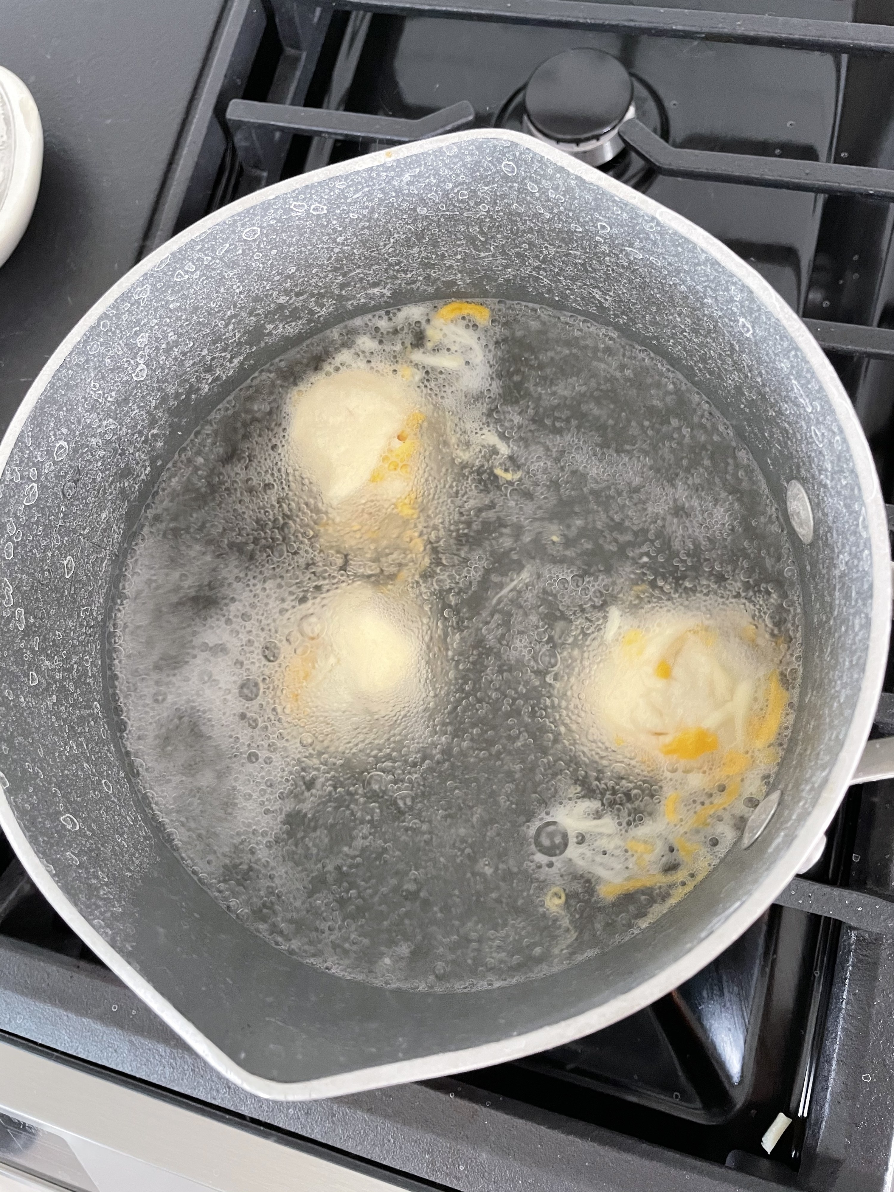 Pretzel dough balls in a baking soda bath