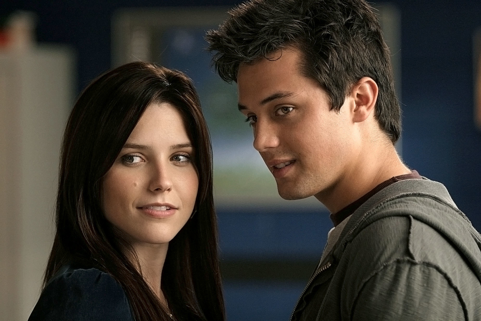On the set of One Tree Hill, actors Sophia Bush and Stephen Colletti smirk, both looking off to the left