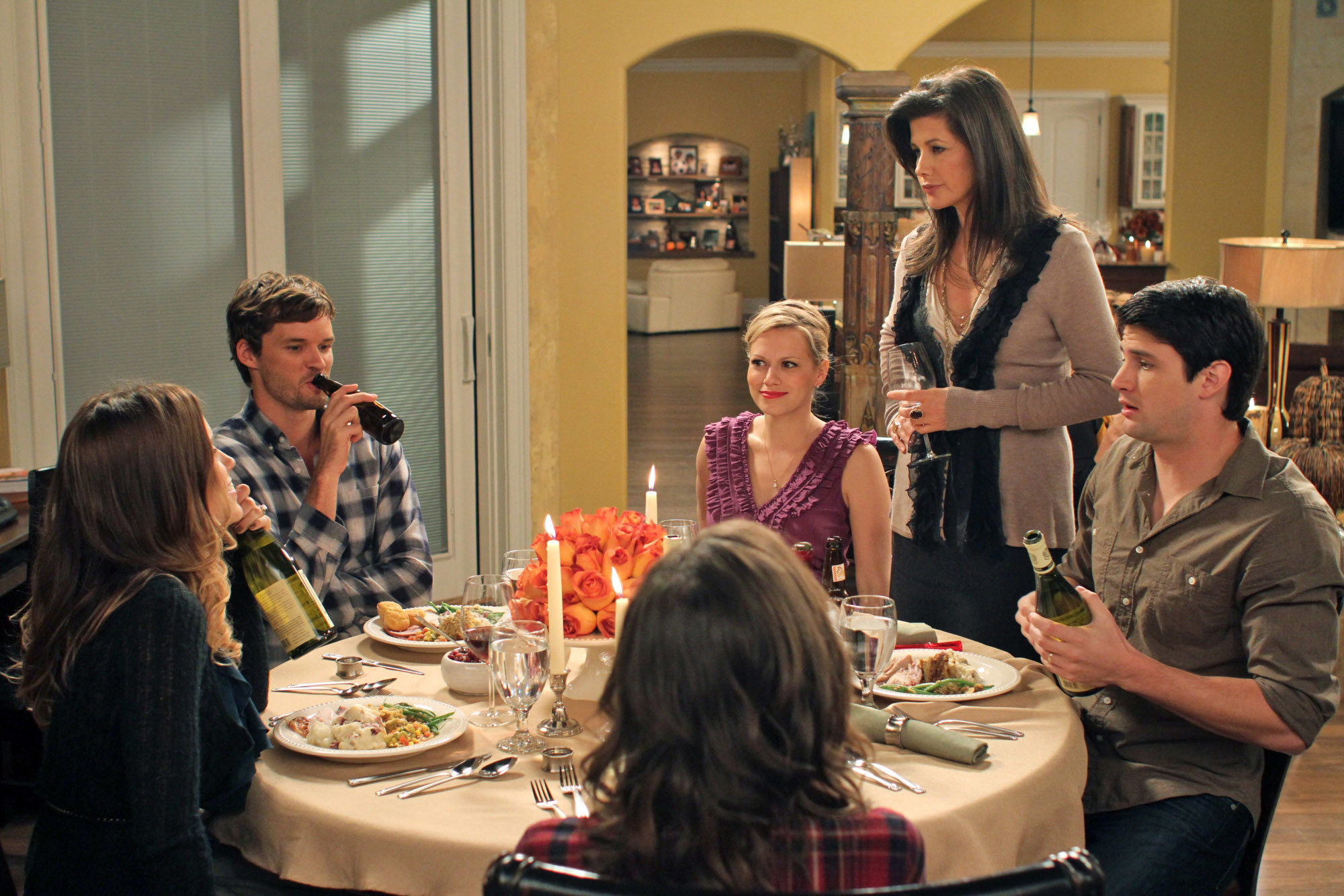 The cast of One Tree Hill sit at the dinner table together: Sophia Bush, Austin Nichols, Kate Voegele, Bethany Joy Galeotti, Daphne Zuniga, and James Lafferty