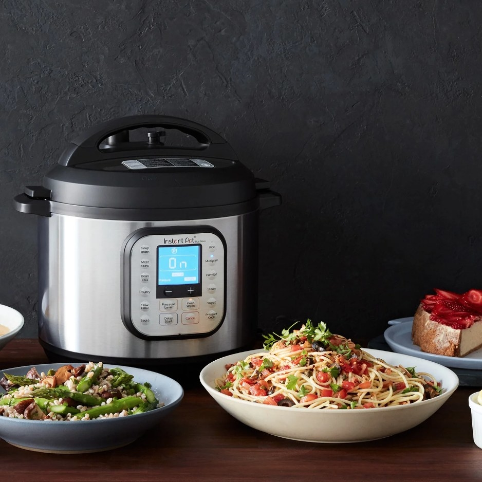 An Instant Pot electric pressure cooker on a counter next to plates of delicious meals