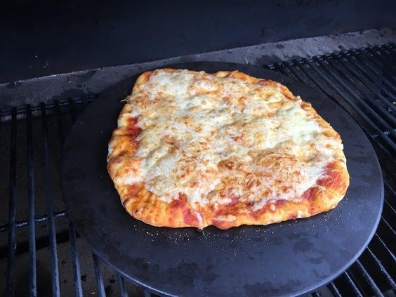 reviewer photo showing a pizza on their grill on the pizza stone