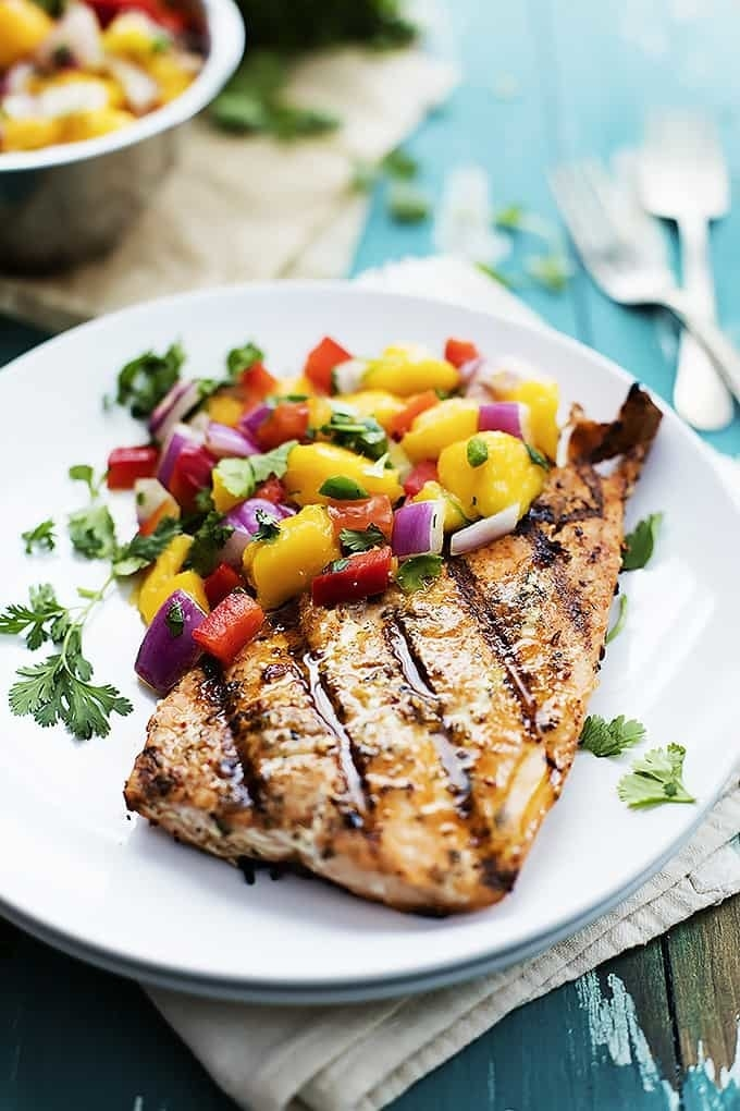 A piece of grilled salmon with mango salsa.