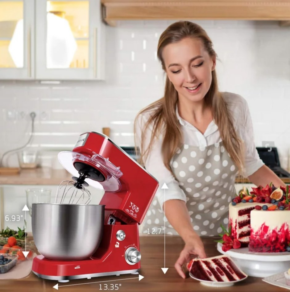 A model using a red, 3-speed stand mixer in the kitchen next to a red velvet cake