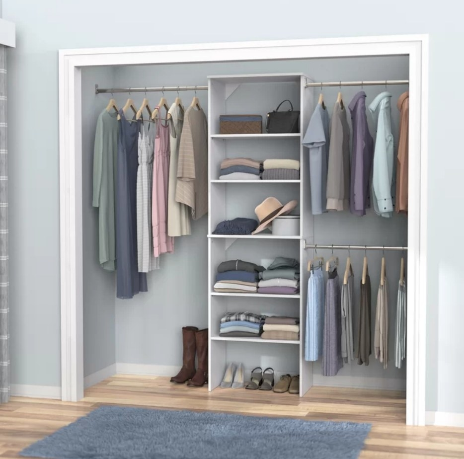 An adjustable closet system with three rods and 5 shelves filled with clothing inside a closet