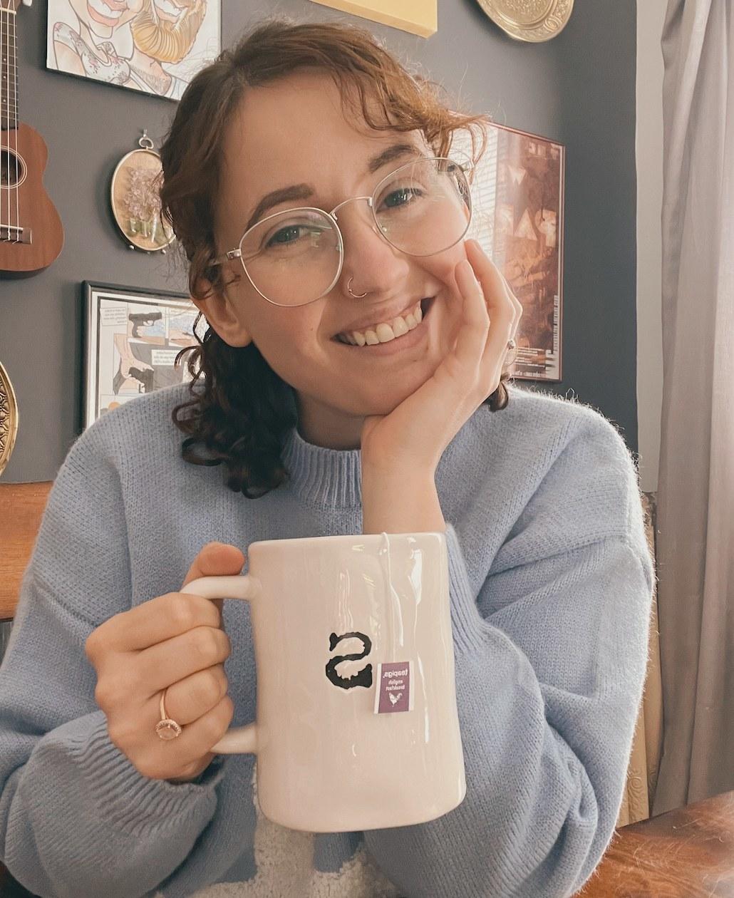 A person holding a mug of hot tea