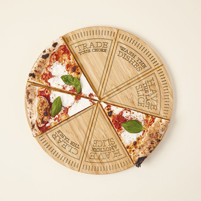 Round pizza slicing board with several pieces removed, revealing the tasks underneath