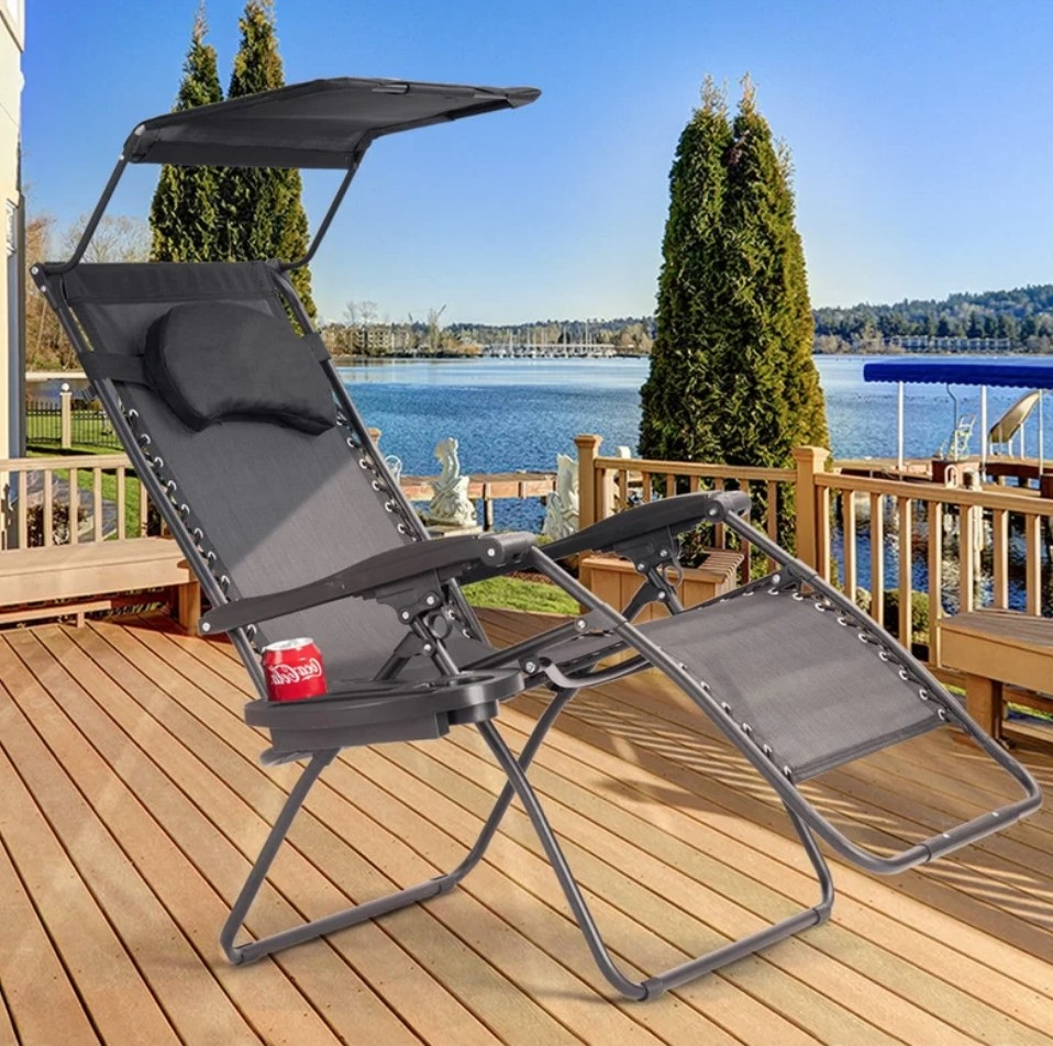 A grey, reclining outdoor chaise with a removable pillow and an umbrella  on a deck