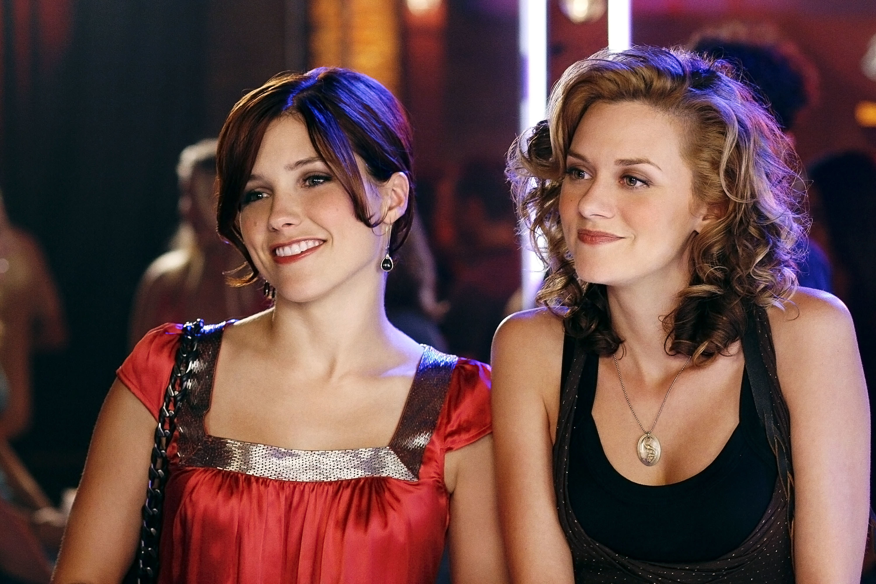 On set of One Tree Hill, actors Sophia Bush and Hilarie Burton smile, dressed up in club attire