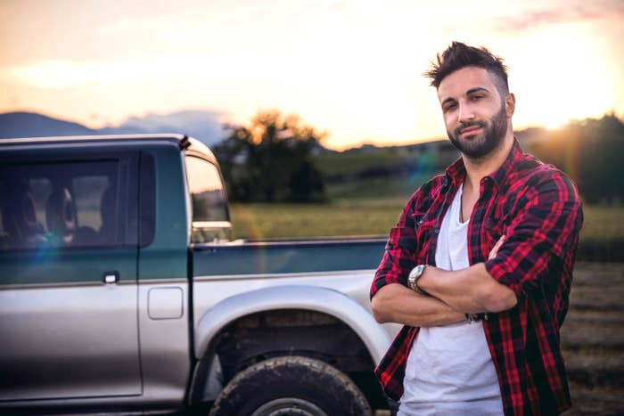 Man standing next to a truck while wearing a plaid shirt