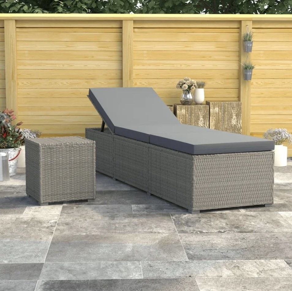 A grey, reclining outdoor chaise with a grey cushion next to a matching side table on a patio