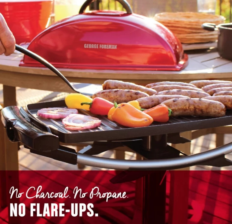 A red, non-stick, George Foreman grill cooking veggies and sausages