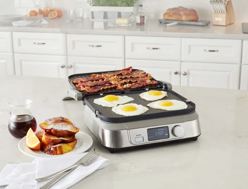 A silver, non-stick, Cuisinart griddler on a kitchen counter filled with eggs and bacon