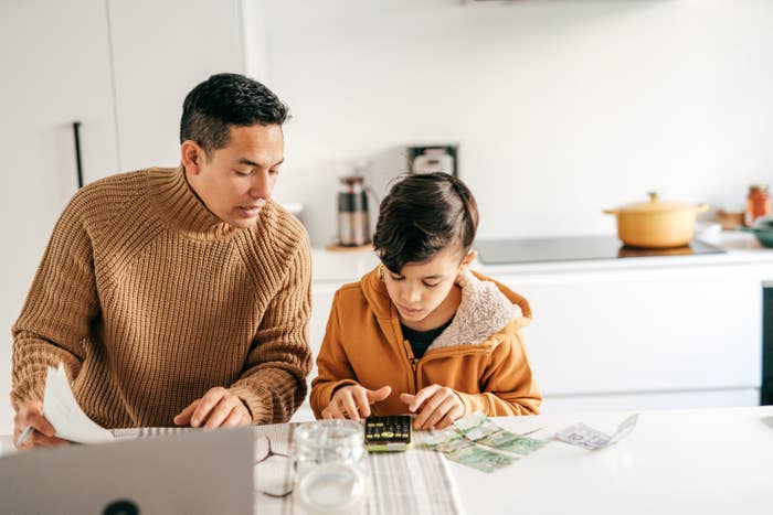 Young dad and child counting cash and using a calculator as part of a financial lesson at home