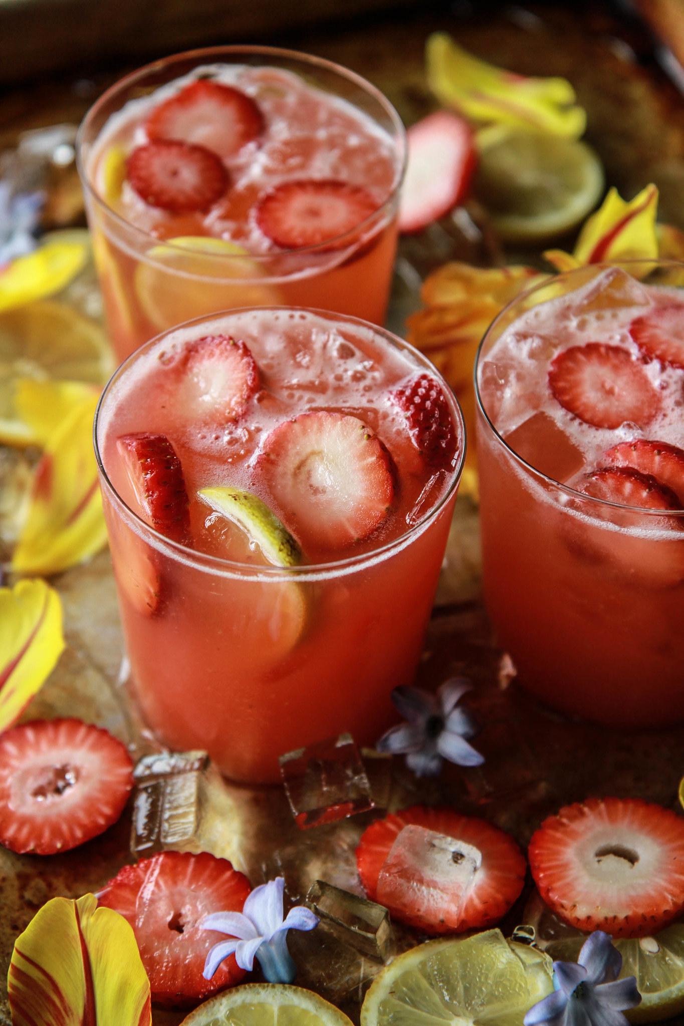 Three glasses of strawberry vodka lemonade with fresh berries and lemon.