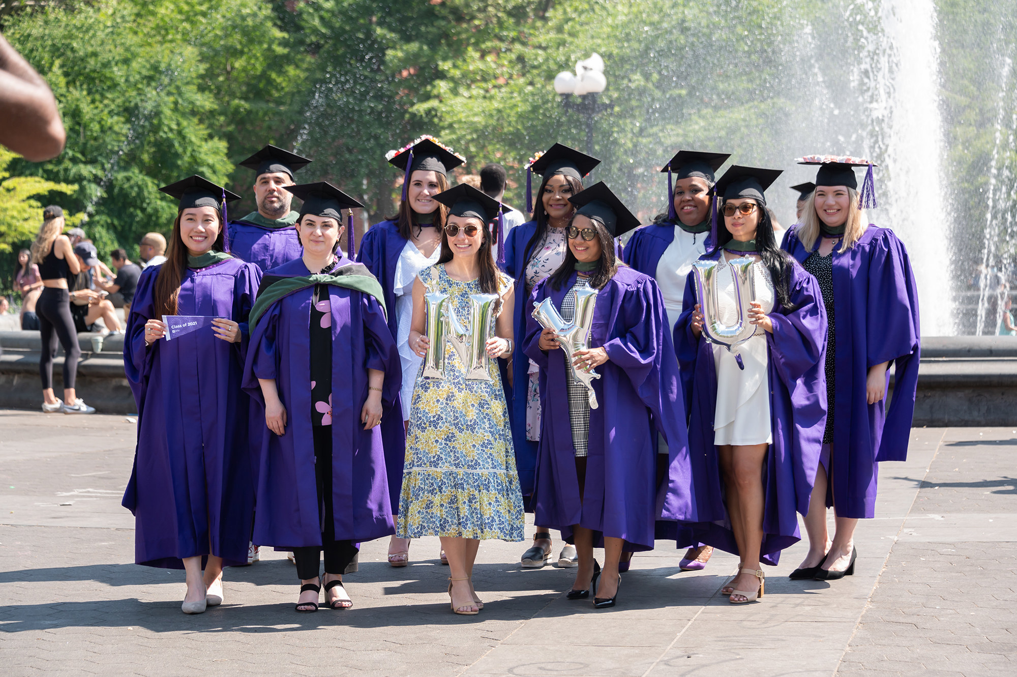 A group of NYU graduates in purple robes and graduation caps stand in front of a fountain