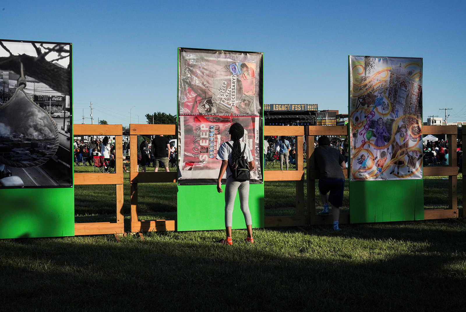 A woman stands behind a fence by three tall vertical artworks that depict the Tulsa massacre through photography, collage, and paint