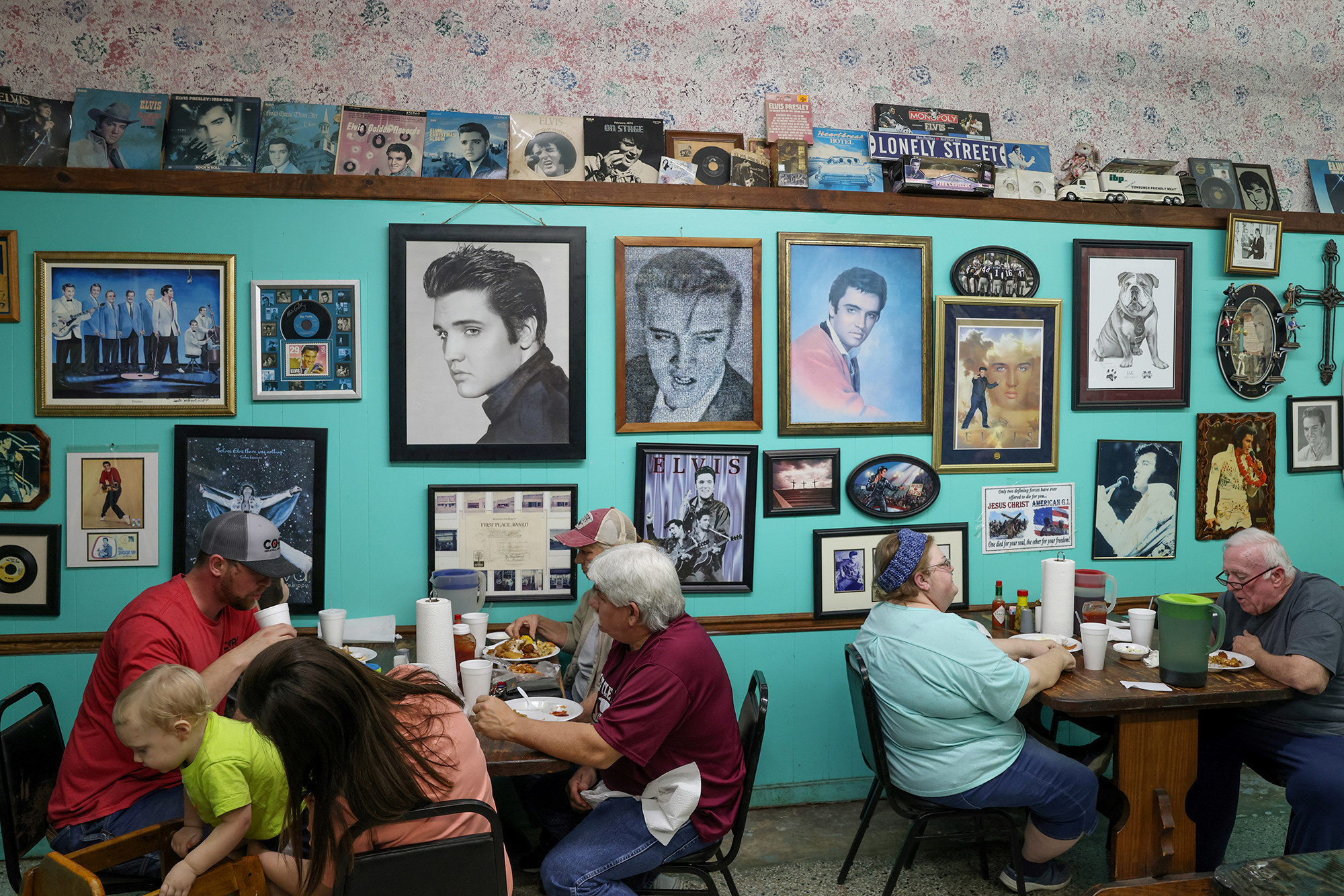 People gather maskless indoors at a restaurant with many pictures of Elvis on its walls