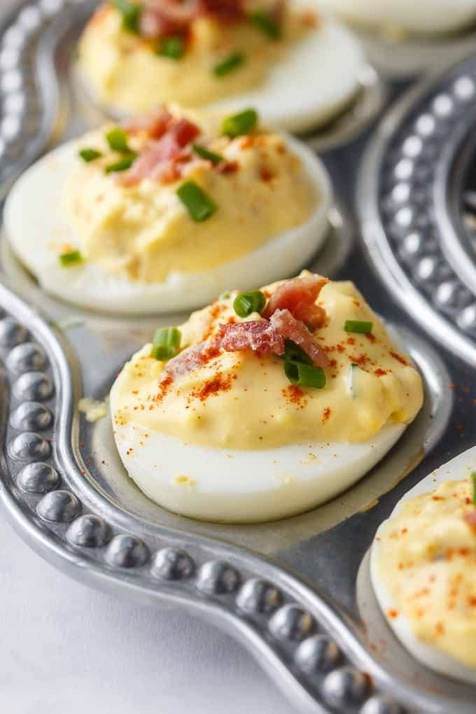 Deviled eggs topped with bacon and chives.