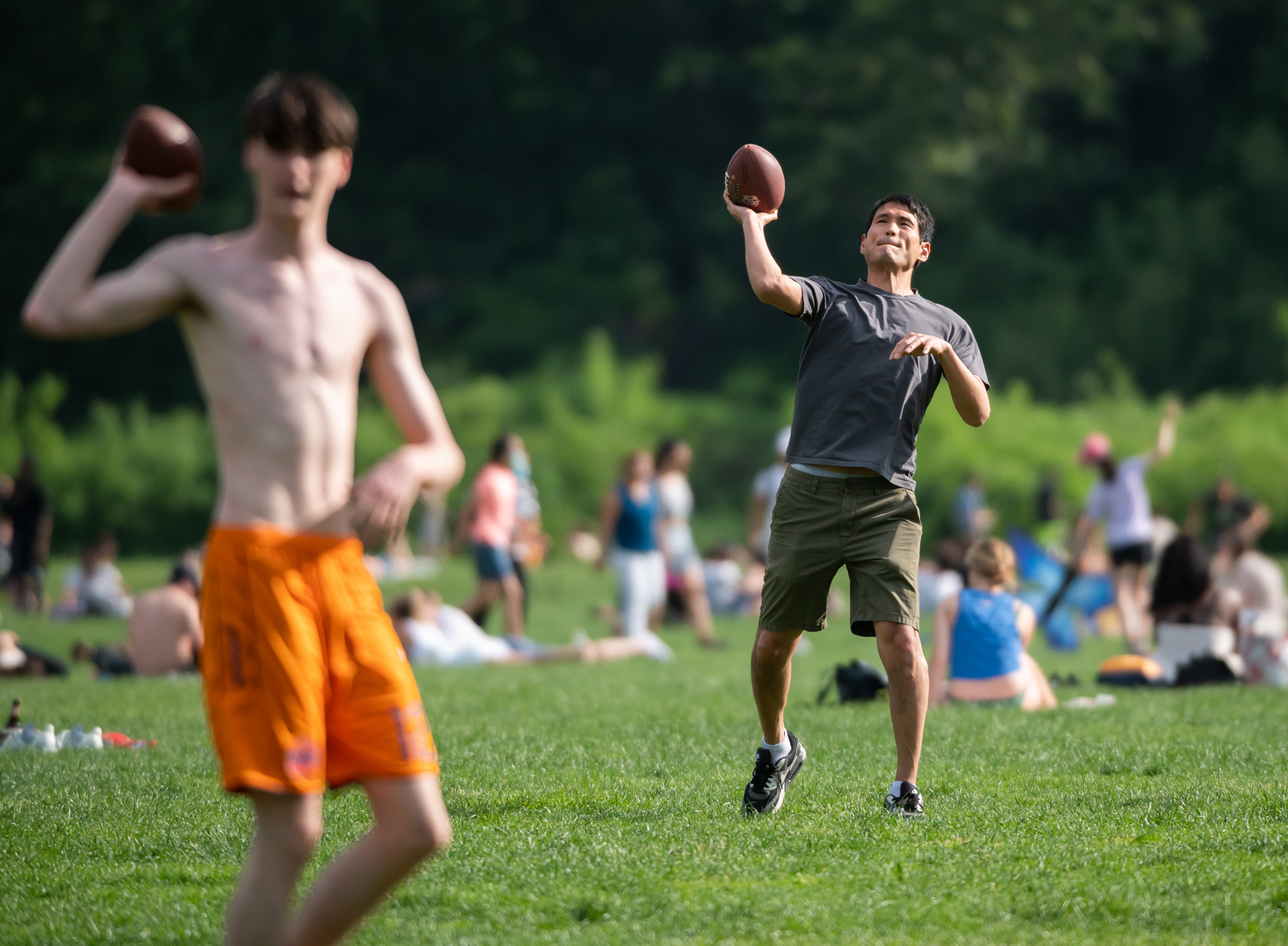 Two men in shorts throw footballs past the camera