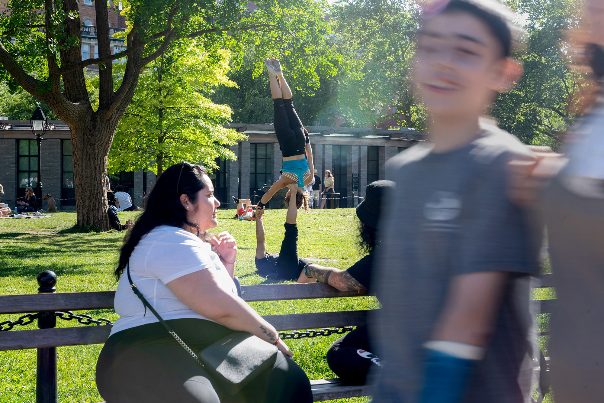 A woman on a bench with her friend watch a couple do acro-yoga, and a boy walks through the forefront of the camera