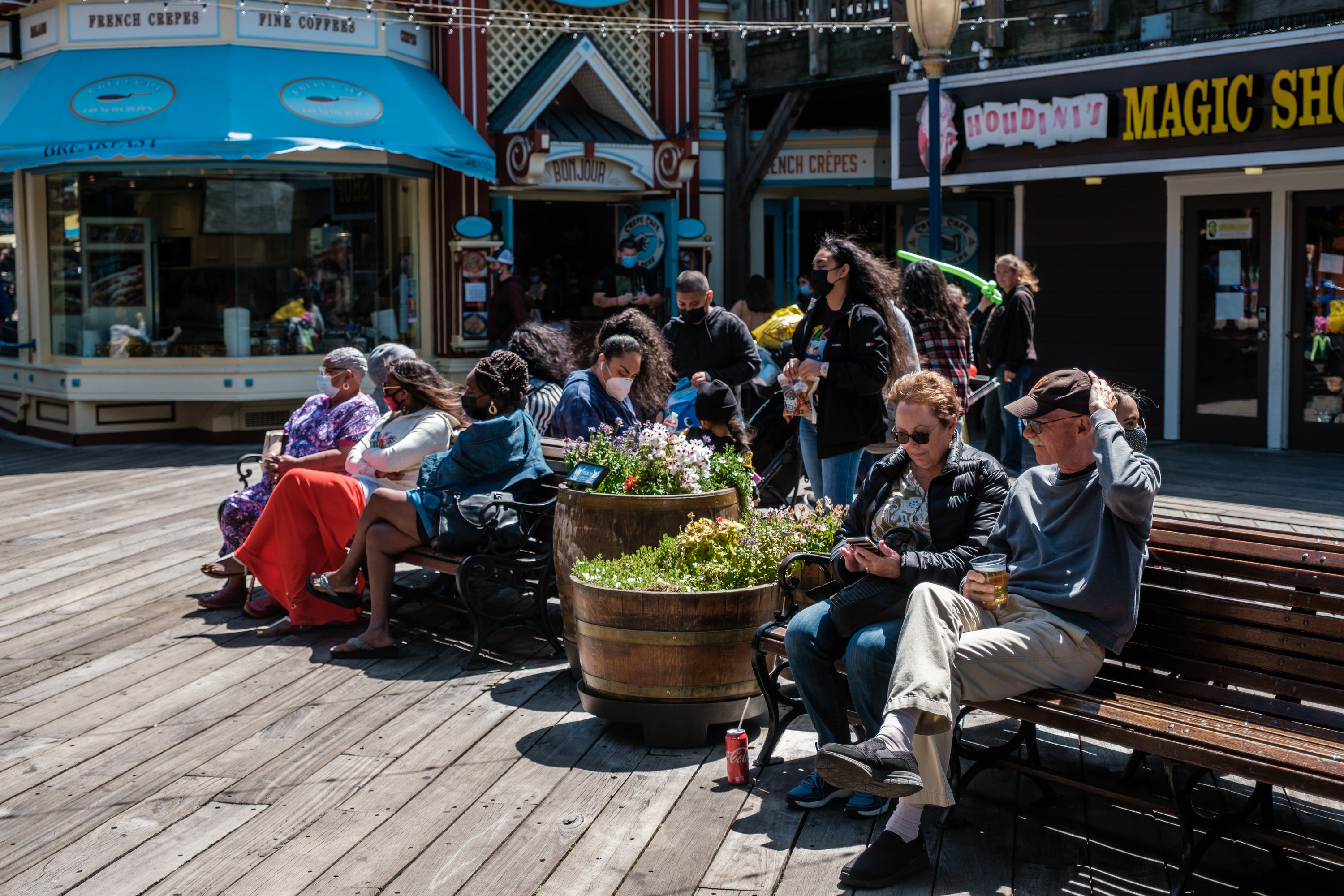 Groups of people sitting on benches in the sunshine on Fisherman's Wharf, some are unmasked