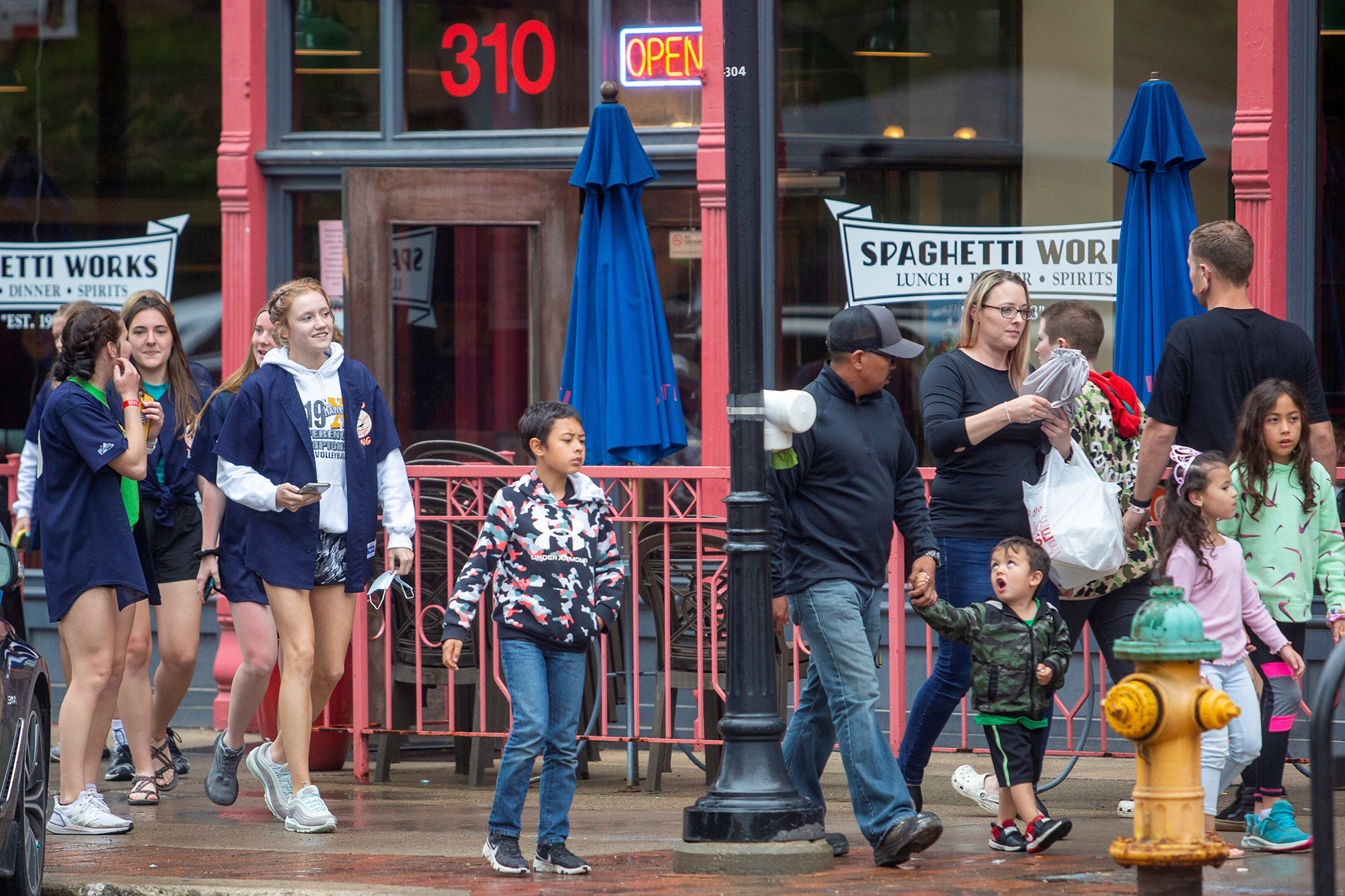 Groups of maskless people walk downtown in Des Moines on a rainy day