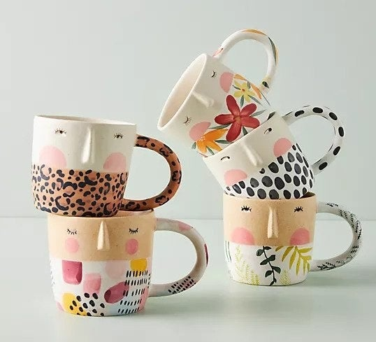 Several mugs that look like faces with outfits on
