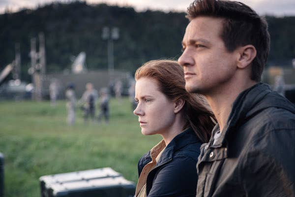Amy Adams and Jeremy Renner staring into the distance