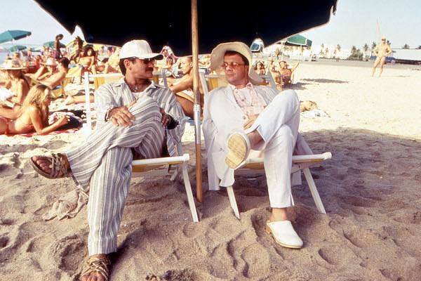 Robin Williams and Nathan Lane lounging at the beach.