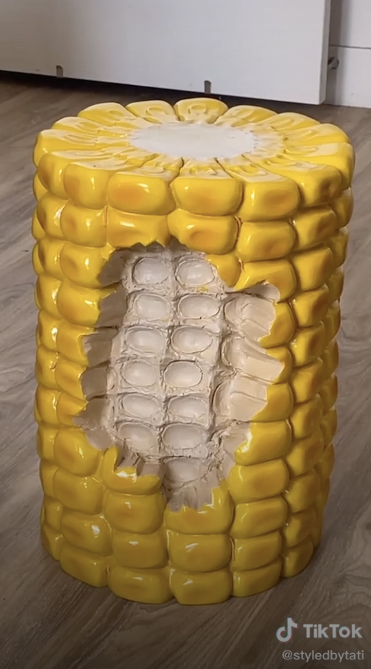 An end table that looks like corn on the cob with a bite taken out of it
