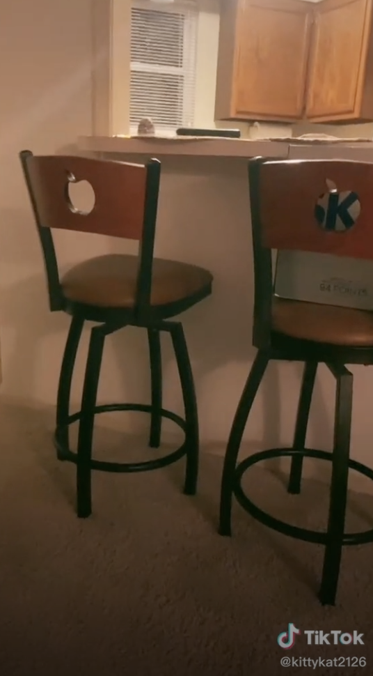 Two wooden barstools with the Applebee's logo carved out of their back panels