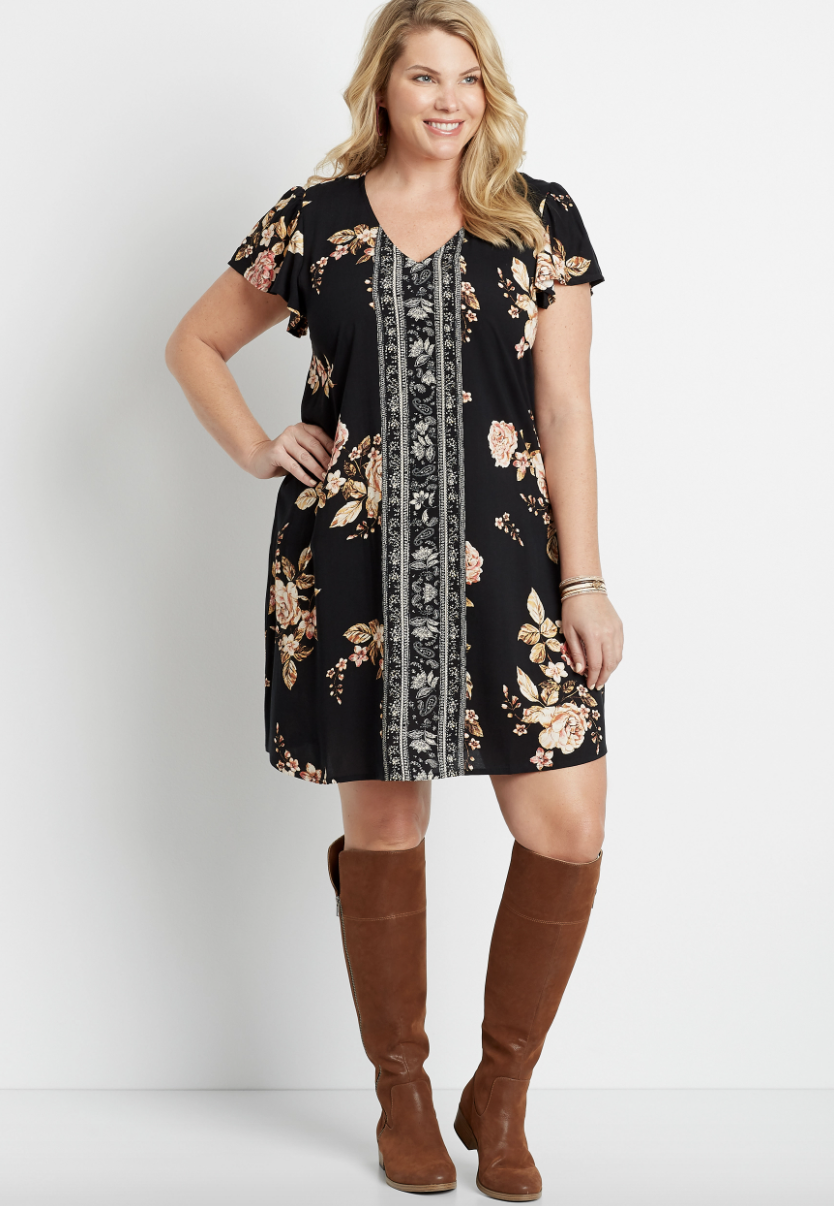 model wearing short sleeve above the knee black dress with a floral pattern