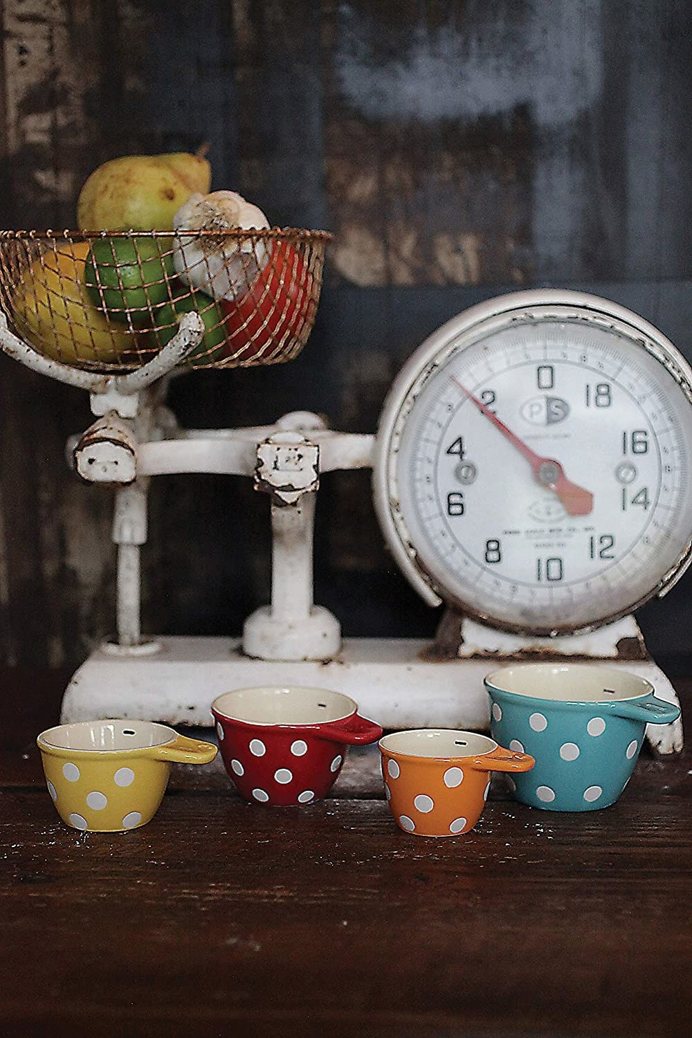 Four polka dot measuring cups in front of a decorative cooking scale