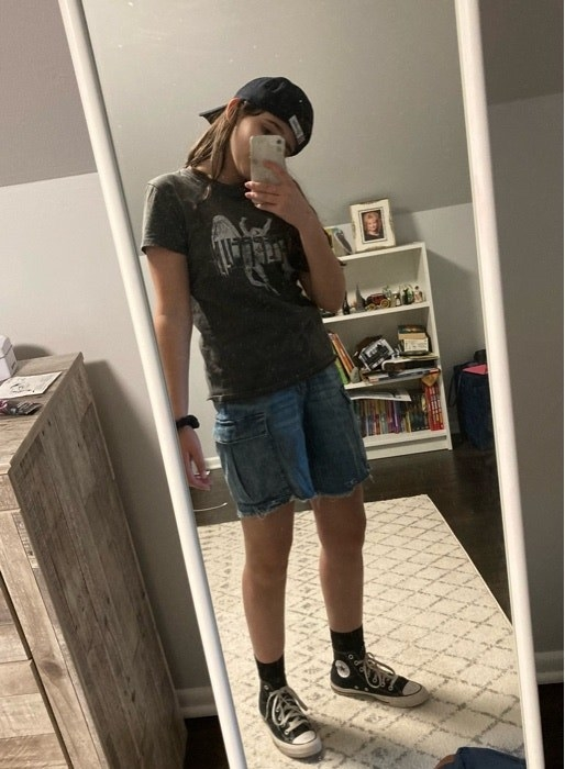 BuzzFeed user taking a mirror selfie while wearing a backwards hat, Led Zeppelin t-shirt, jean shorts, and converse sneakers
