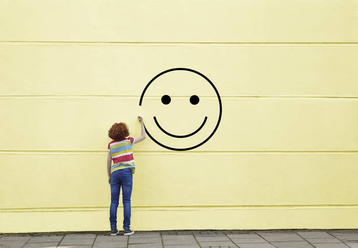 A person in jeans and a striped t-shirt painting a smiley face on a wall