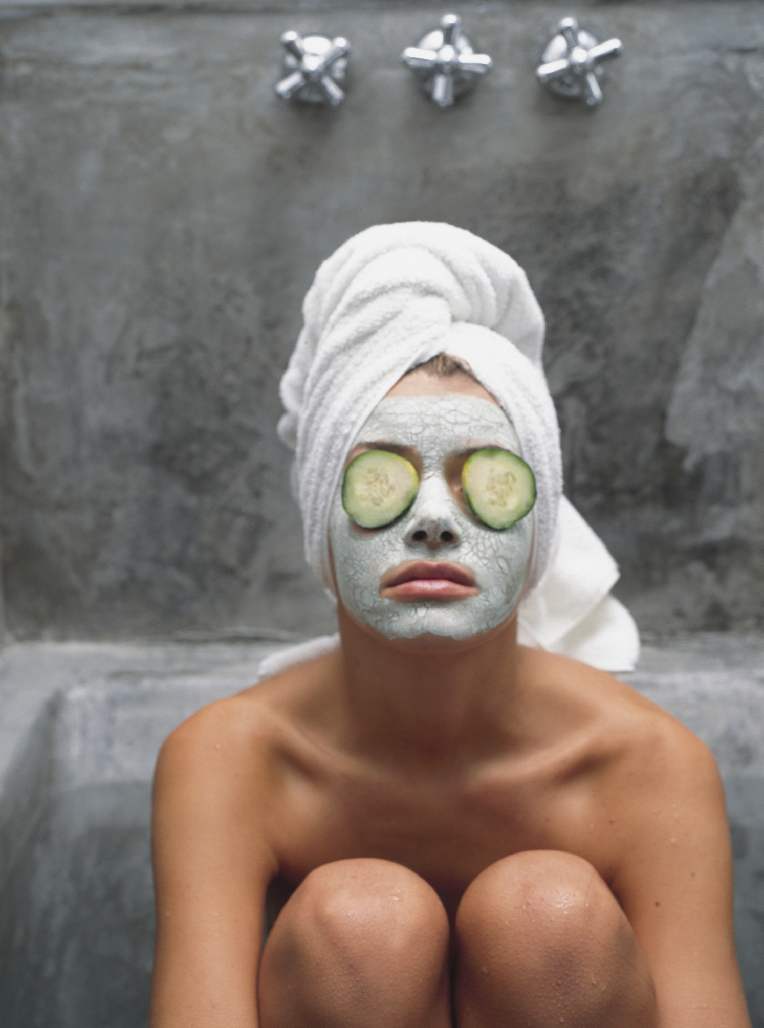 Woman sitting in a spa room with a face mask on and cucumber slices over her eyes, hair wrapped up in a towel