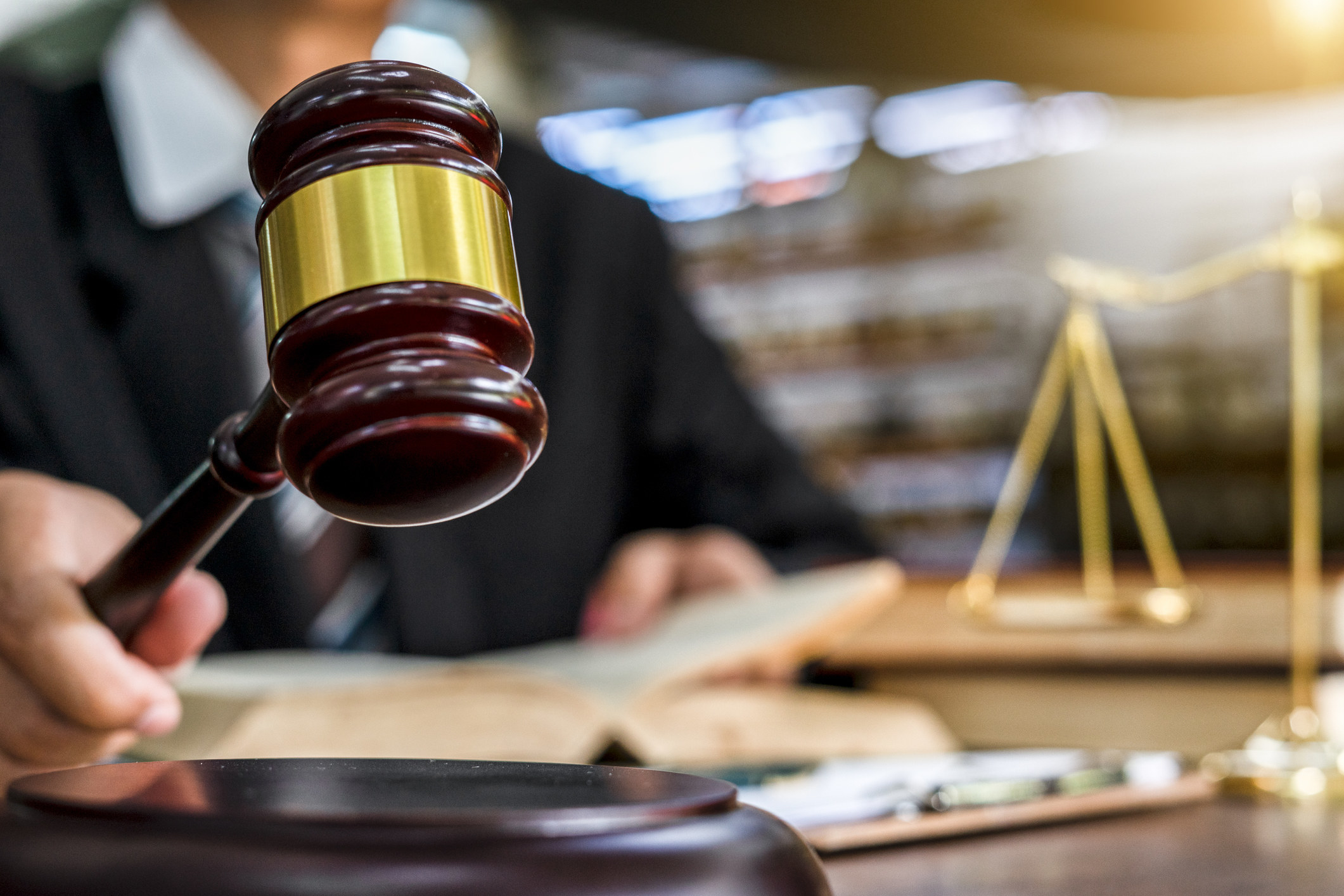 Close-up of a gavel being held by a judge-type holding a book, about to strike a sound block. Golden scales of justice sit on a table in the background