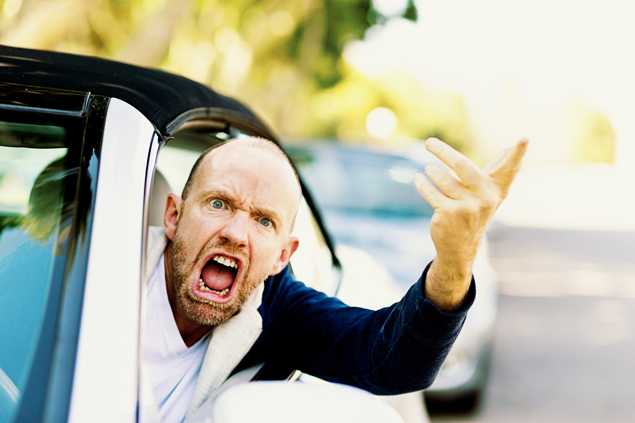 Man leaning out the driver's seat of a car shouting and pointing