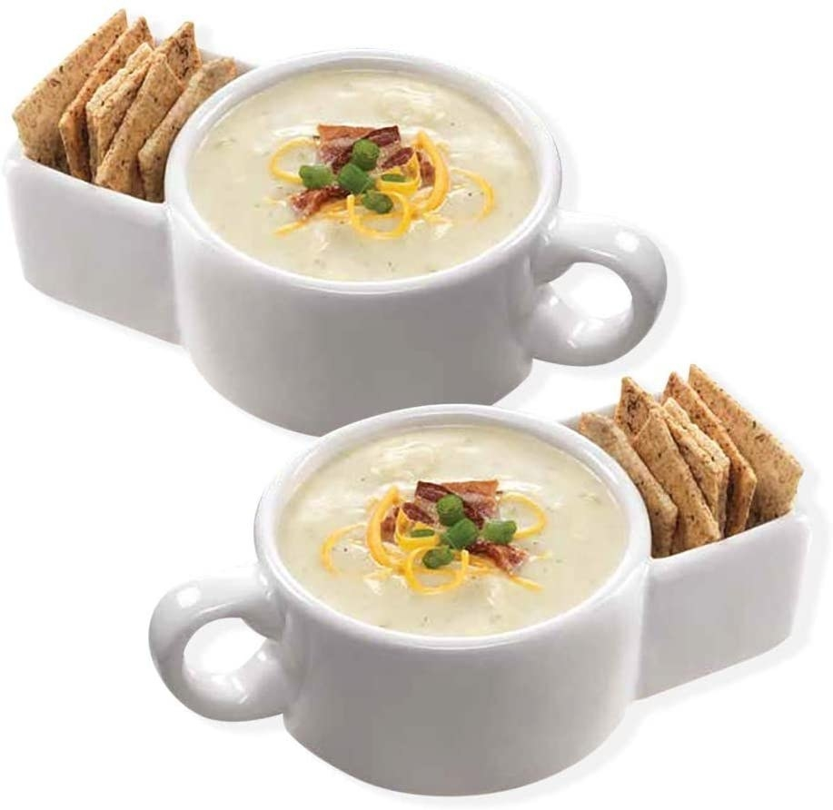 a white ceramic mug with soup in the round part and crackers in the side slot