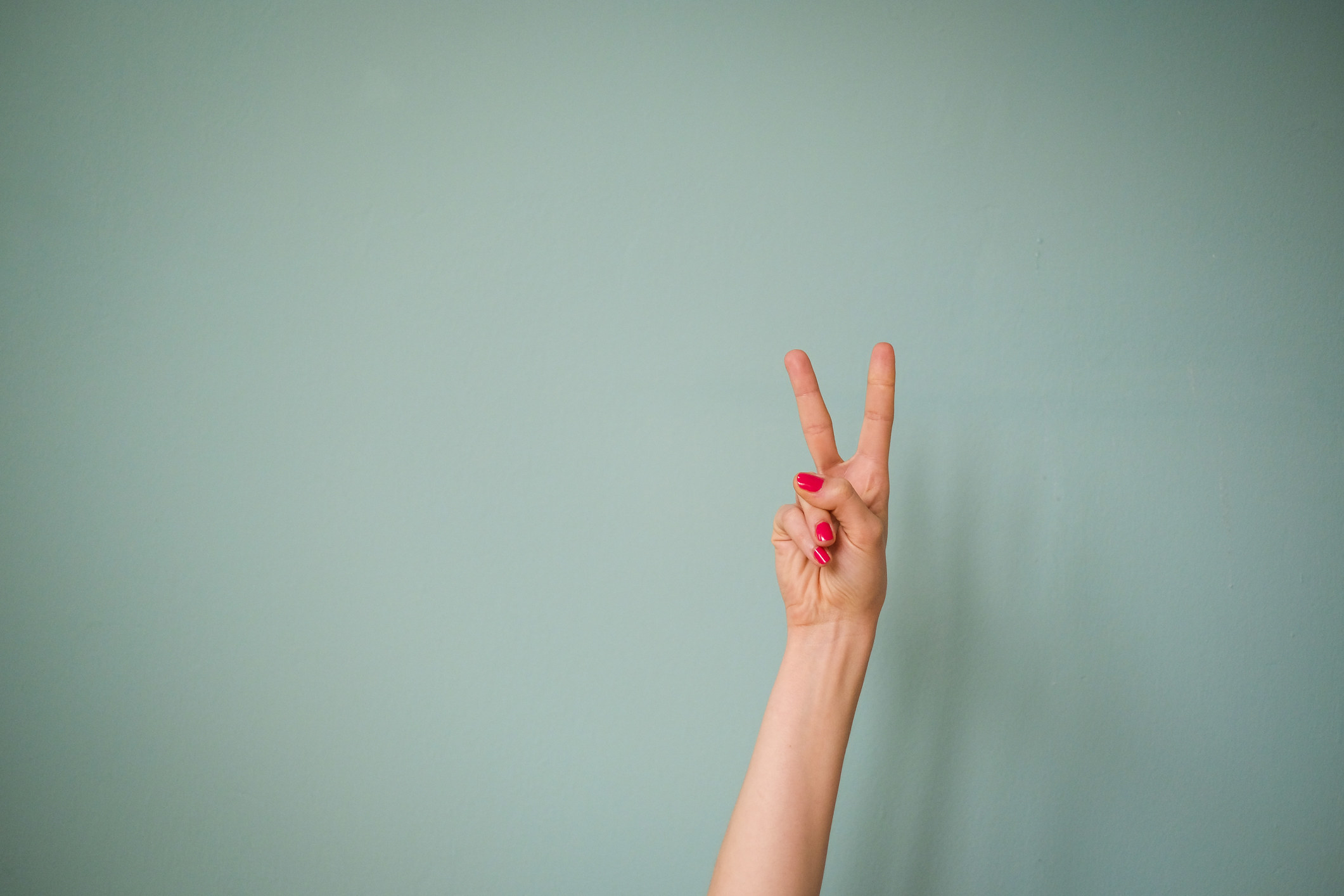 A person holding the peace sign with her nails painted red against a mint colored call