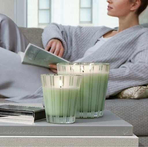 two green candles burning in the front while a model reads in the background