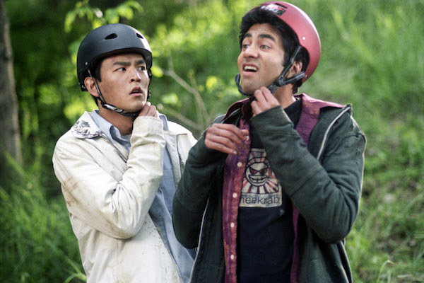 John Cho and Kal Penn taking off their helmets.