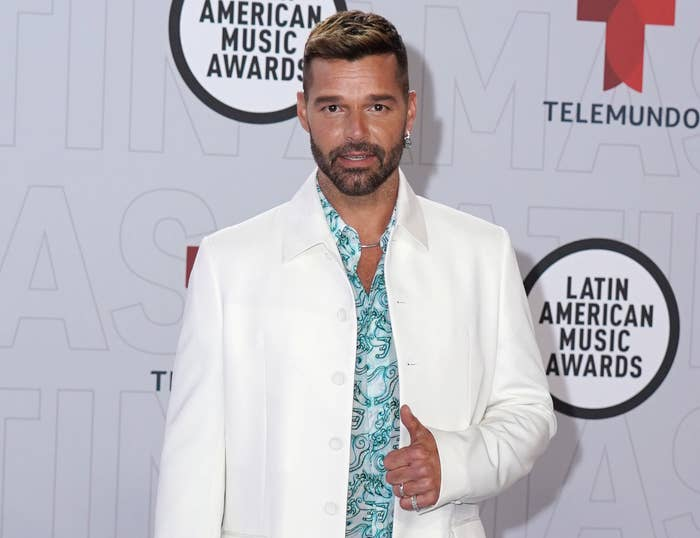Ricky wears a white suit jacket and turquoise button up