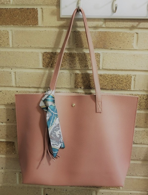 A reviewer's blush tote bag hanging on a hook